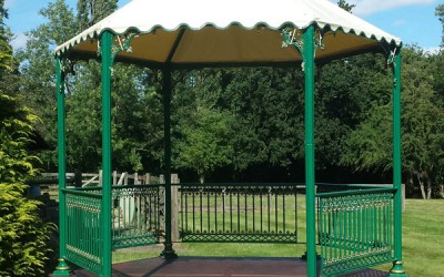 Green and gold Victorian bandstand with canopy and stage